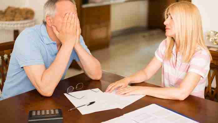 Worried couple calculating their expenses